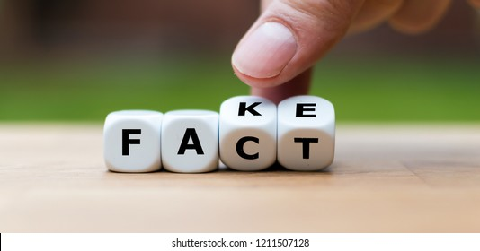 Hand is turning a dice and changes the word FAKE to FACT
