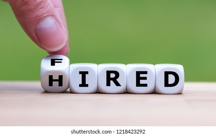 """Hand is turning a dice and changes the word """"fired"""" to """"hired"""""""