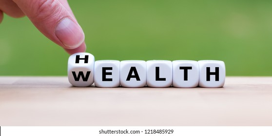 "Hand is turning a dice and changes the word ""Health"" to ""Wealth"""