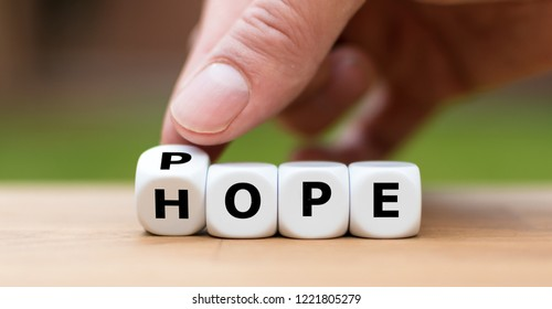 """Hand is turning a dice and changes the word """"hope"""" to """"pope"""""""