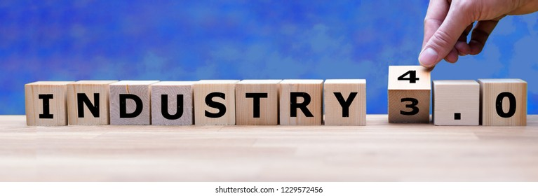 """Hand is turning a dice and changes the word """"Industry 3.0"""" to """"Industry 4.0"""""""