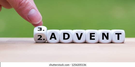 """Hand is turning a dice and changes the word """"2.Advent"""" to """"3.Advent"""" as symbol for the upcoming third Advent"""
