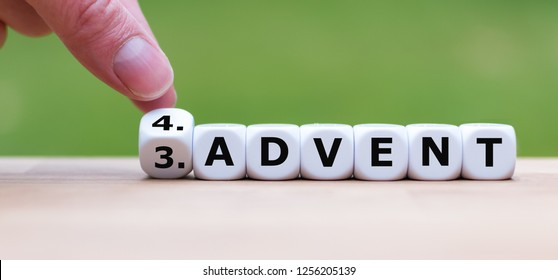 """Hand is turning a dice and changes the word """"3.Advent"""" to """"4.Advent"""" as symbol for the upcoming fourth Advent"""
