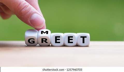 """Hand is turning a dice and changes the word """"Meet"""" to """"Greet"""""""