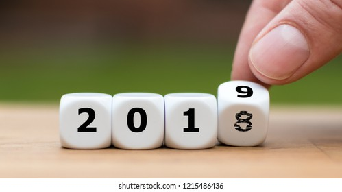 Hand is turning a dice and symbolically changes the year 2018 to 2019