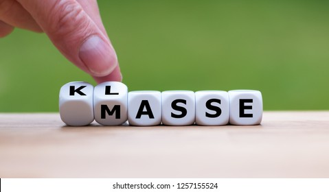 """Hand is turning dices and changes the German word """"Masse"""" to """"Klasse"""". It stands for quality instead of quantity"""