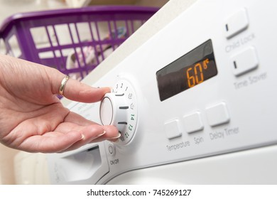 Hand turning the knob of a clothes dryer to adjust temperature