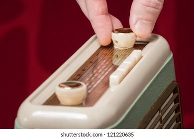 Hand turning knob on old vintage radio