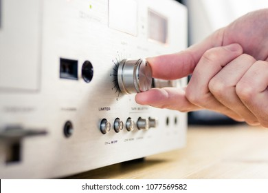 Hand turning a knob on a vintage hi-fi equipment
