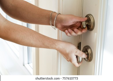 Hand turning lock on front door of house