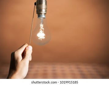 Hand turning off the bulb lamp