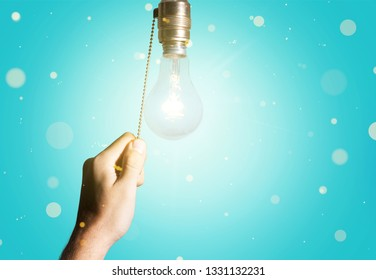 Hand turning off the bulb lamp, blue background