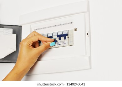 Woman's hand turning off electrical fuse box