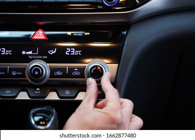 Hand turning on car's air conditioner dial. Hand adjusting heater temperature button.