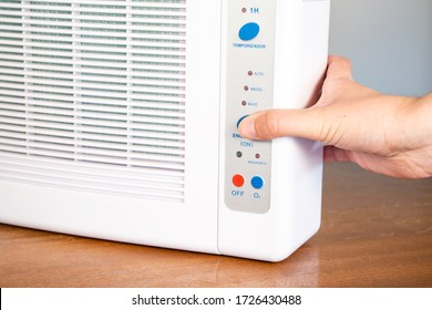 Hand turning on ozone machine generators to cleaning and disinfection during covid 19 epidemic. Details in Spanish. - Shutterstock ID 1726430488