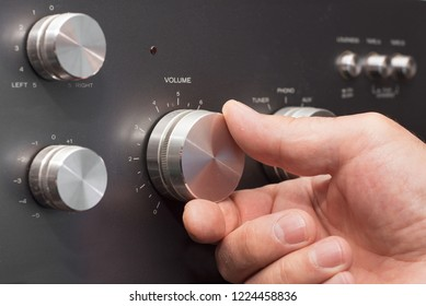 Hand turning up the volume in a stereo