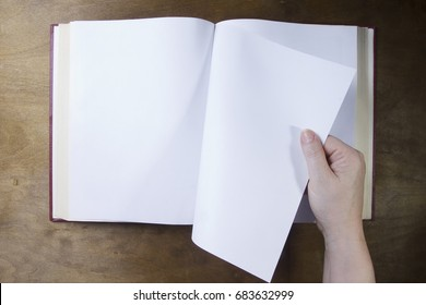 Hand turns the blank sheet of books on a wooden table