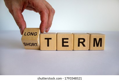 Hand turns a cubes and changes the expression 'SHORT TERM' to 'LONG TERM' or vice versa. Beautiful white background. Business concept, copy space.
