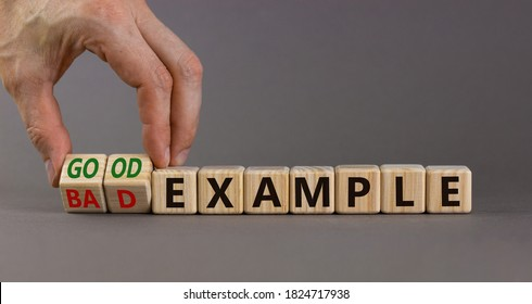 Hand turns a cubes and changes the expression 'bad example' to 'good example'. Beautiful grey background. Business concept. Copy space.
