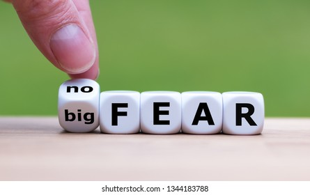 "Hand turns a dice and changes the expression ""big fear"" to ""no fear""."
