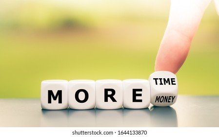 """Hand turns dice and changes the expression """"more money"""" to """"more time"""".  - Shutterstock ID 1644133870"""