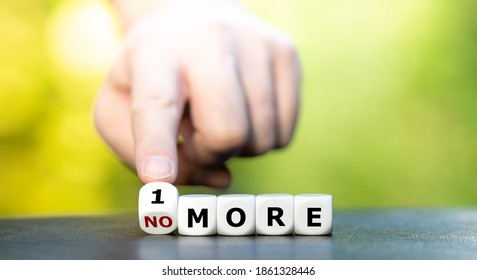 """Hand turns dice and changes the expression """"no more"""" to """"1 more"""". - Shutterstock ID 1861328446"""