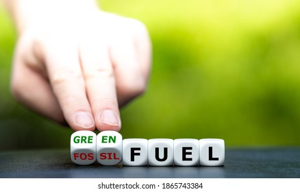 """Hand turns dice and changes the expression """"fossil fuel"""" to """"green fuel""""."""