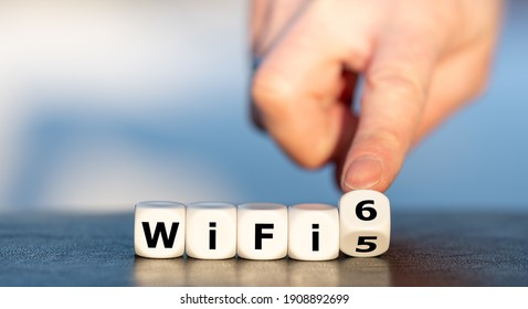 """Hand turns dice and changes the expression """"WiFi 5"""" to """"WiFi 6""""."""