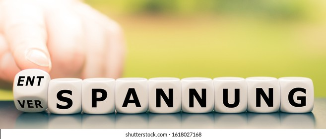 """Hand turns a dice and changes the German word """"Verspannung"""" (""""tenseness"""" in English) to """"Entspannung"""" (""""relaxation"""" in English). - Shutterstock ID 1618027168"""