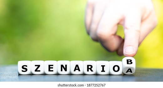 "Hand turns dice and changes the German expression ""szenario A"" (scenario A) to ""szenario B"" (scenario B)."
