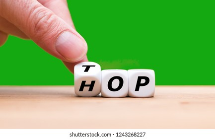 """Hand turns a dice and changes the word """"Hop"""" to """"Top"""""""