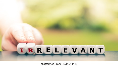 Hand turns dice and changes the word irrelevant to relevant.