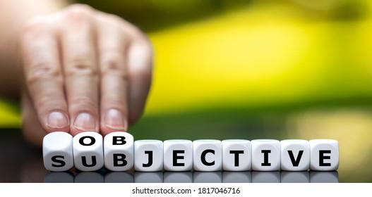 """Die Hand dreht Würfel und ändert das Wort """"subjektiv"""" in """"objektiv""""."""