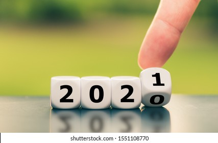 """Hand turns a dice and changes the year """"2020"""" to """"2021""""."""