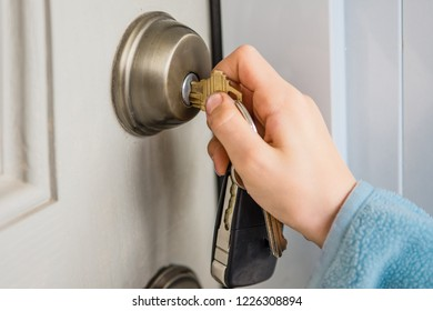 The hand turns the key in the door lock of the front door to the house