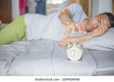 Hand turns off the alarm clock waking up at morning . soft skin tone effect