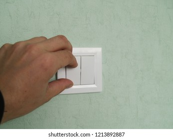hand turns off the light on the switch located on the wall