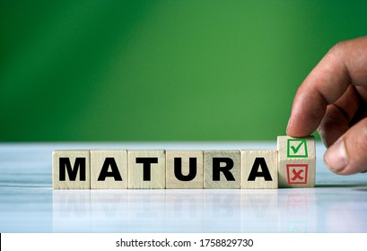 The hand turns the wooden cube and changes the polish word MATURA (english = secondary school certificate) with green positive tick check box and red reject X check box.