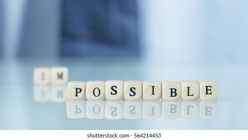 "A hand turns the word ""Impossible"" to ""Possible"" throwing away the letters. Concept: commitment, believe it until the end, everything is possible."