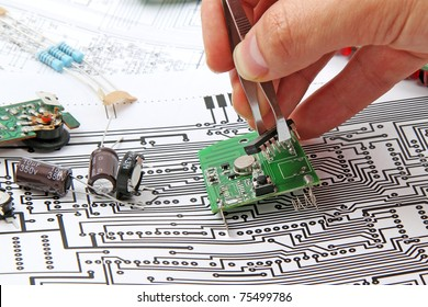 A hand hand with tweezers holding a electronic circuit board  on the background of electronic scheme