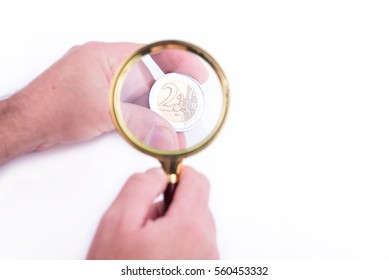 Hand with a two euro coin magnified by a magnifying glass on white background