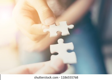 Hand of two people holding jigsaw puzzle connecting together. Concept of partnership and teamwork in business strategy