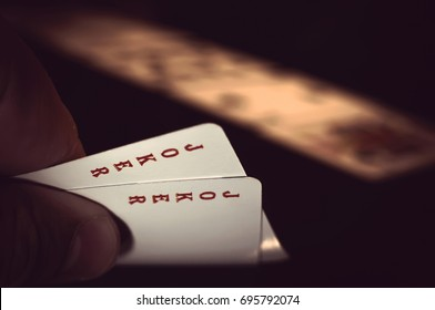 Hand with two playing cards showing jokers over a black background