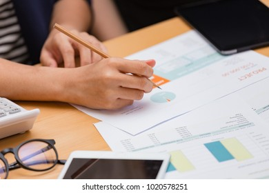 Hand of two women working on monthly budget with calculator, tablet,  glasses and notebook on table