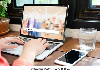 Hand tying labtop computer with www. on search bar over blur store background on screen, on line shopping ,business, E-commerce, technology and digital marketing concept background