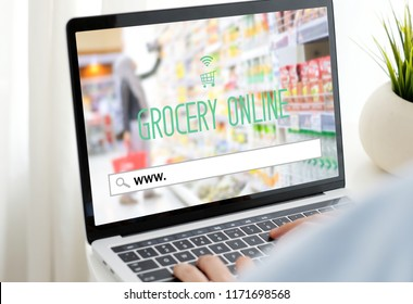 Hand tying laptop computer with www. on search bar over blur grocery store background on screen, grocery on line shopping ,business, E-commerce, technology and digital marketing concept background
