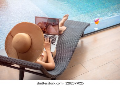 hand typeing on notebook keyboard of woman bikini at swimming pool, working on line communation to the jobsite