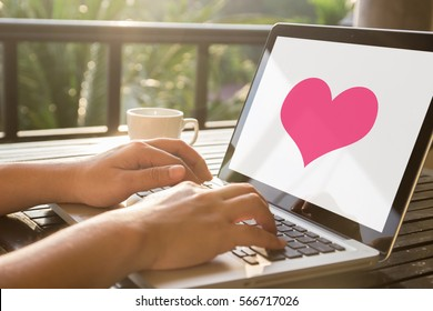 Hand typing a computer laptop and heart screen with white background on the wooden table. Find or choose love couple concept. Valentine day.