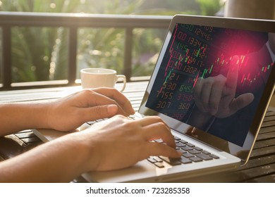 Hand typing a computer laptop trade stock and investor advice sell stock with red point color on screen