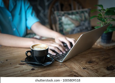 Hand typing laptop with coffee